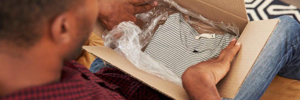 Homme ouvrant un carton de vêtements